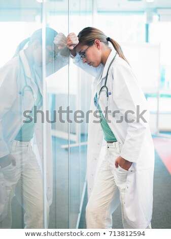 Concerned doctor leaning on glass wall Stock photo © IS2