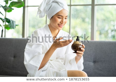 A beautiful young girl in a white robe is sitting at a table Stock photo © Traimak
