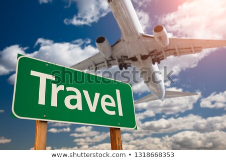 travel green rodd sign with airplane flying above stock photo © feverpitch