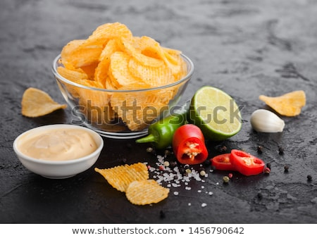 Glass bowl plate with potato crisps chips with onion flavour on black stone table background. Red an stock photo © DenisMArt