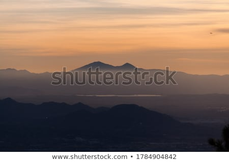 Airplane is flying over mountains in fog at colorful sunset Stock photo © denbelitsky