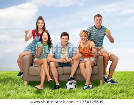 friends or soccer fans with ball and drinks in sky stock photo © dolgachov