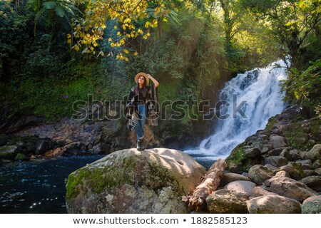 Stock photo: Woman Stands On Rock In Front Of Cascading Waterfall