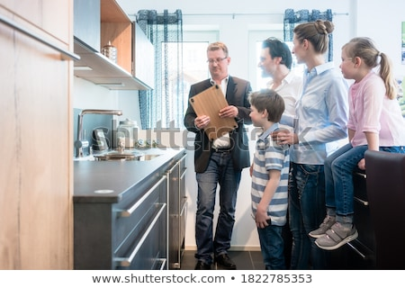 Family with kids looking at a kitchen in showroom Stock photo © Kzenon