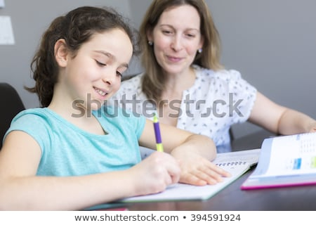 mature mother helping her child with homework at home stock photo © lopolo