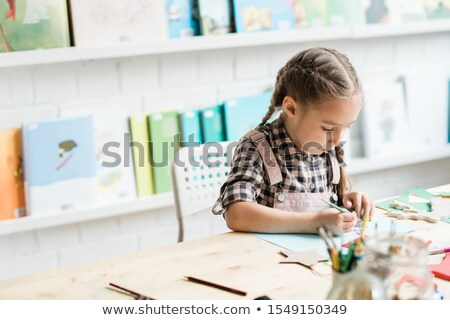 diligent schoolgirl drawing christmas picture by desk while working individually stock photo © pressmaster