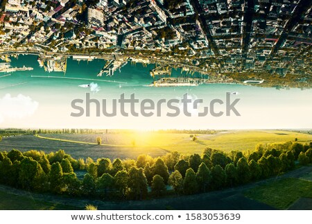 Natural landscape with unreal upside down sityscape. Stock photo © artjazz
