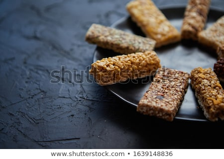 Different kind of granola fitness bars placed on black ceramic plate on a table Stock photo © dash