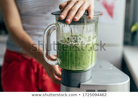 Process of preparing green detox smoothie with blender, young man hands cooking healthy smoothie. Stock photo © Illia