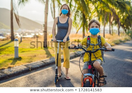 Active school kid boy and his mom riding a bike with backpack on sunny day. Happy child biking on wa Stock photo © galitskaya