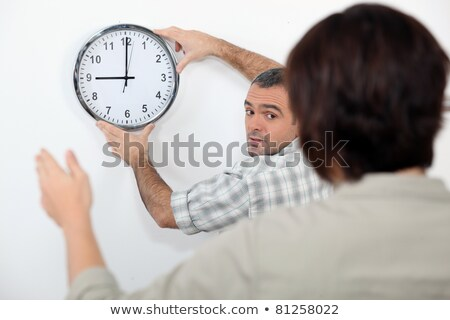 Couple straightening a crooked clock Stock photo © photography33