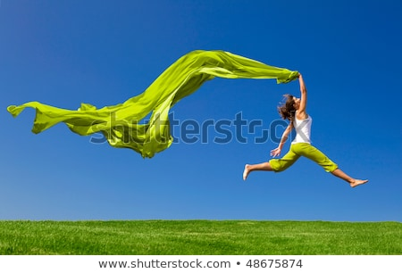 Woman jumps in a green field Stock photo © Nobilior