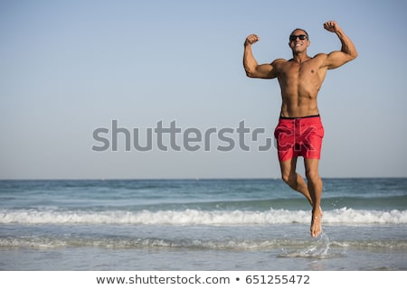 Sorridente sem camisa muscular homem em pé branco Foto stock © wavebreak_media