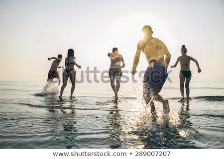 happy young couple having fun running on beach at sunset stock photo © dashapetrenko