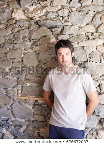 man leaning on rock wall in chalet Stock photo © IS2