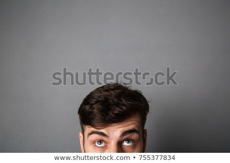 Cropped photo of young man with short haircut looking upward Stock photo © deandrobot