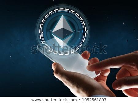 businessman with smartphone and ethereum hologram Stock photo © dolgachov