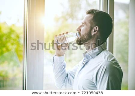 Barbado hombre potable botella agua cómico Foto stock © rogistok