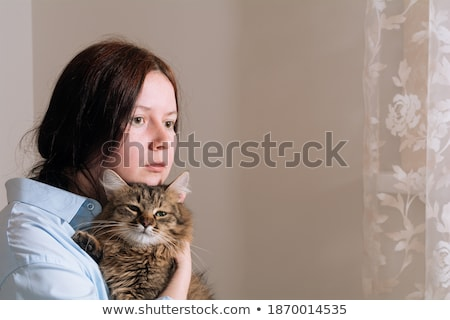 Young woman with cute little kitten sitting on bed at home Stock photo © dashapetrenko