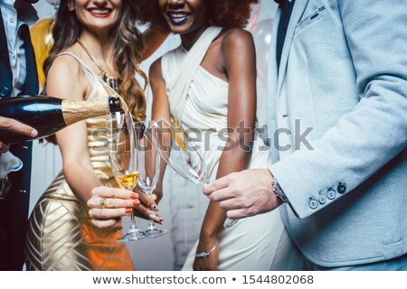 Stock photo: Man pouring sparkling wine into glass of his friends celebrating a party