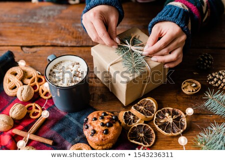 Hands of girl making knot on top of wrapped giftbox surrounded by sweet food Stock photo © pressmaster