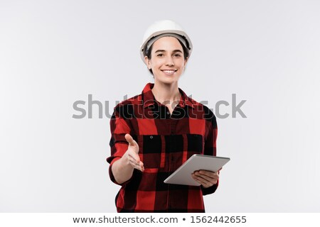 Happy young female architect in hardhat and flannel welcoming you by handshake Stock photo © pressmaster