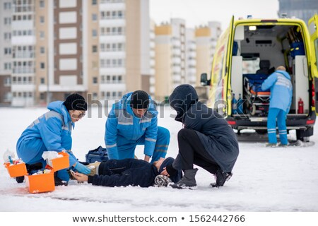Two paramedics in uniform and guy giving first aid to sick unconscious man Stock photo © pressmaster