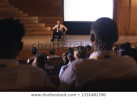 Front view of Caucasian businessman sitting on a wheelchair and giving presentation to the audience  Stock photo © wavebreak_media