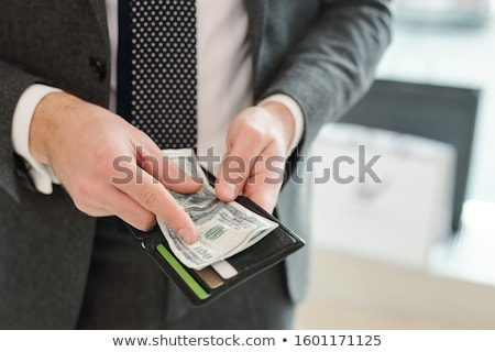 Hands of rich elegant businessman in suit holding wallet and dollar banknotes Stock photo © pressmaster