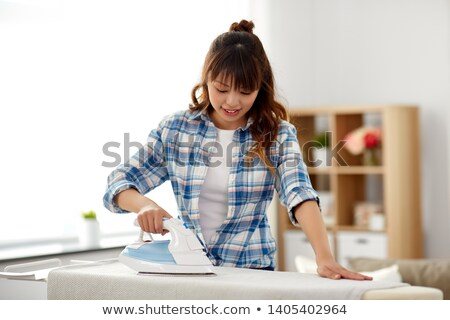 asian woman or housewife ironing bed linen at home Stock photo © dolgachov