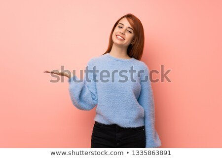 Redhead girl showing something stock photo © Noedelhap