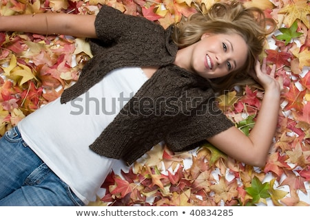 Blond woman laying in leaves Stock photo © photography33