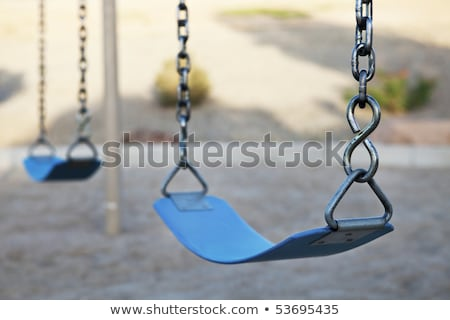 portrait of pretty young woman swinging on playground at park an stock photo © hasloo