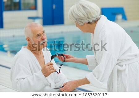 Elderly couple lying on inflatable mattress on a pool deck Stock photo © photography33