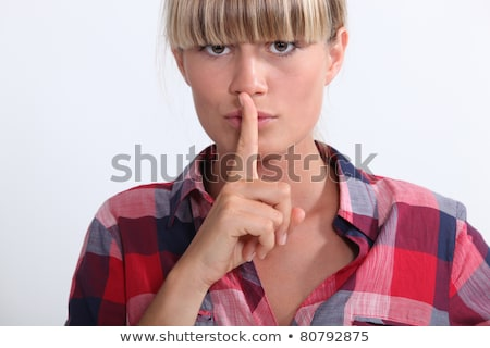 Young woman with a blunt fringe holding her finger to her lips Stock photo © photography33