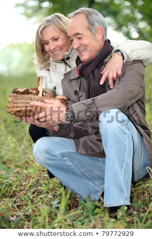 old couple watching a wickerwork basket of mushrooms in the countryside Stock photo © photography33
