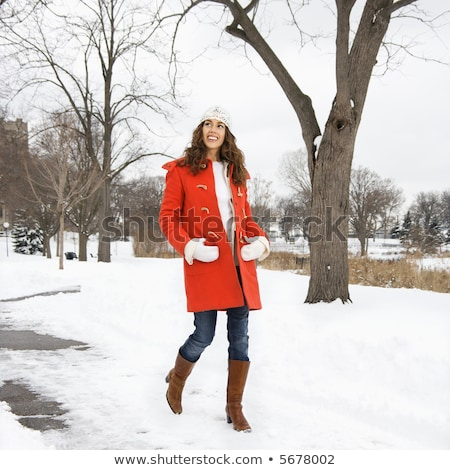 Stock photo: Young woman walking down snow covered street