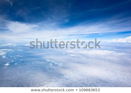 airplane in clouds above earth stock photo © imaster
