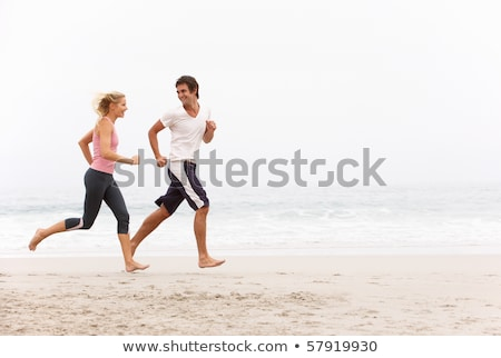young man running along winter beach stock photo © monkey_business