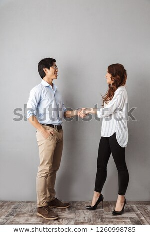Stock photo: Happy businessman offering handshake on gray background