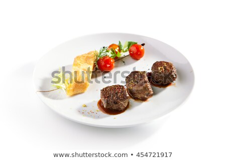 medallion on a plate with slices of tomato Stock photo © OleksandrO