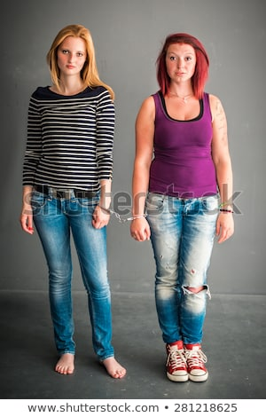 Two angry women connected by a pair of handcuffs Stock photo © uleiber