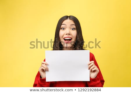 Young businesswoman holding sheets of paper on white background studio stock photo © ambro
