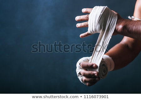 muscular boxer bandaging his hands on gray background Stock photo © master1305