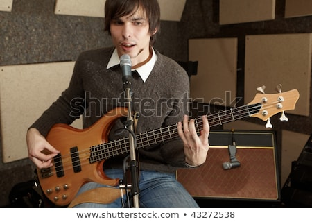 Guitar player is playing and singing in studio. focus on guitar head stock photo © Paha_L