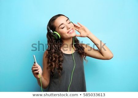 Stok fotoğraf: Cheerful Beautiful Young Woman In Headphones Listening To Music