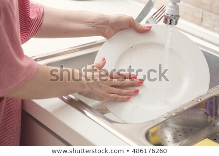 Young woman washing dishes in her modern kitchen Stock photo © lightpoet