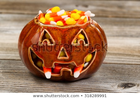 Spooky fanged pumpkin filled with candy corn on rustic wood  Stock photo © tab62