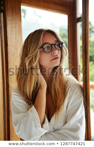Vertical image of casual woman in bathrobe looking away Stock photo © deandrobot