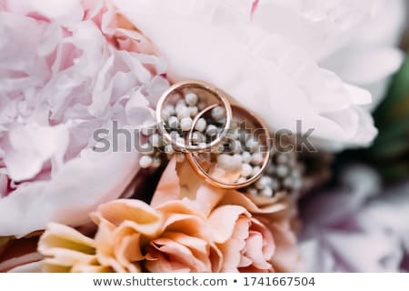 close up view of shiny golden wedding rings on pink wedding rings background stock photo © lightfieldstudios